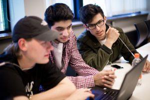 Tre HF økonomi elever, der sidder og kigger på en computer