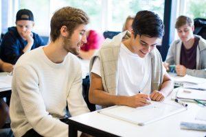 Baggrundsbillede af to elever, som skriver på et whiteboard