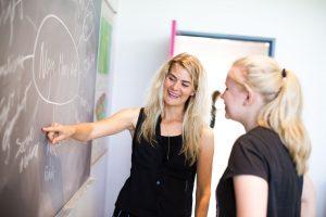 Baggrundsbillede af to elever, der står ved tavlen