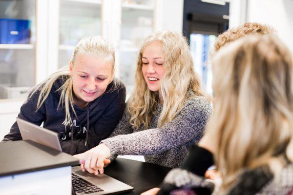 Baggrundsbillede af tre elever, der sidder ved en computer og snakker