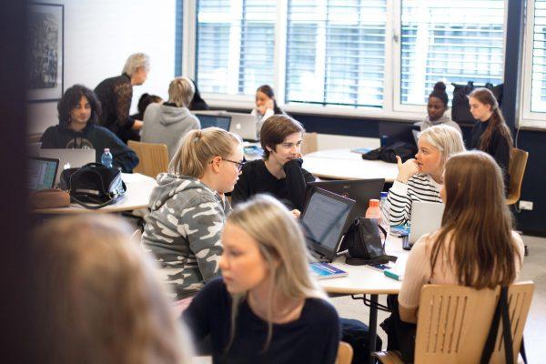 Baggrundsbillede af et klasselokale, hvor eleverne sidder og snakker